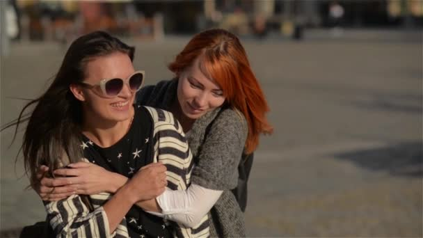 Two girl friends young female friends giving piggyback on vacation laughing and walking in the city, sunny day