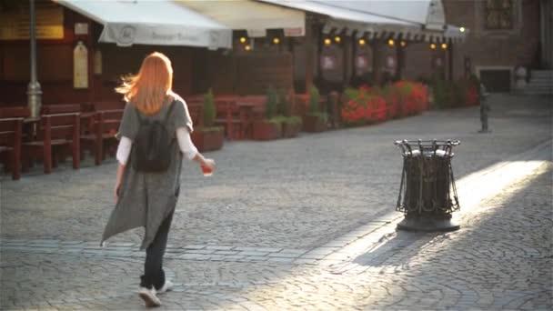 Žena, házení prázdný papír kávy šálek poblíž odpadkový koš, pozadí města. Recyklace, ekologicky šetrný přístup koncept. Udržujte ulice, město, země čisté