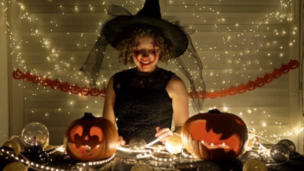 Egy boszinak öltözött, nevető tinilány arcképe ijesztő sminkkel az arcán. A Halloween misztikus sajátosságainak fényében.