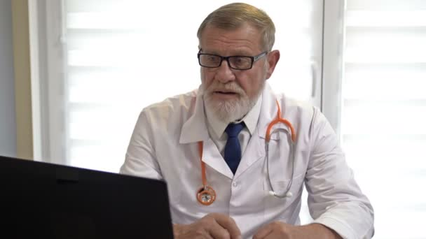 Online doctor. An experienced doctor consults a patient using the laptop. Covid-19 Epidemic.