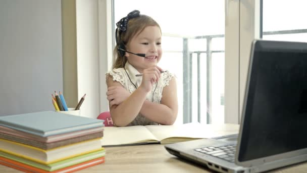 Features of distance learning. Online lesson. Little girl communicates with a teacher via the Internet. Online training during quarantine.