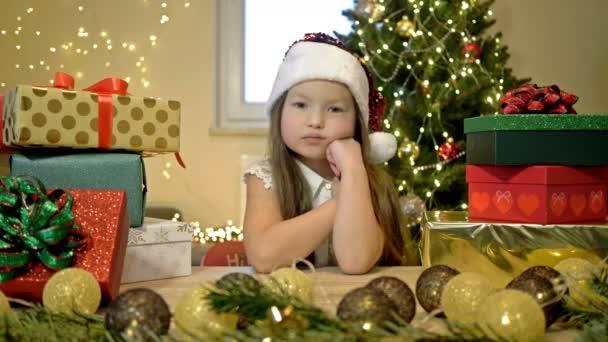 Ein kleines Mädchen mit Weihnachtsmütze sitzt traurig mit dem Kopf auf der Hand. Vor dem Hintergrund eines Weihnachtsbaums und heller Schachteln mit Geschenken. Weihnachtstag.