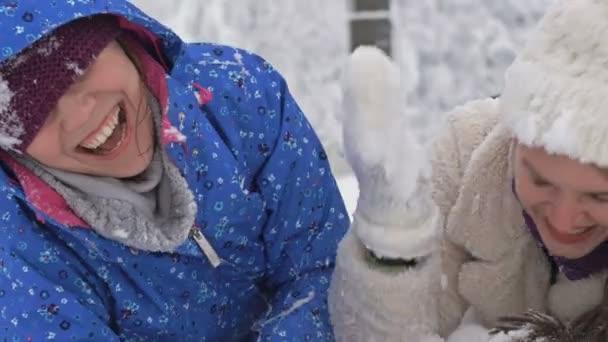 Dvě mladé ženy leží ve sněhu a smějí se. Zimní zábava.