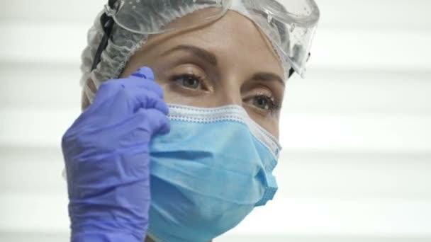 Portrét unavené doktorky nebo sestry. Žena si sundá brýle a masku a s potěšením vypije kávu. Drsný každodenní život zdravotnických pracovníků během pandemie Covid-19.