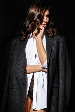 young beautiful brunette woman in a white shirt and the bottom black lingerie and jacket in the studio on a black background