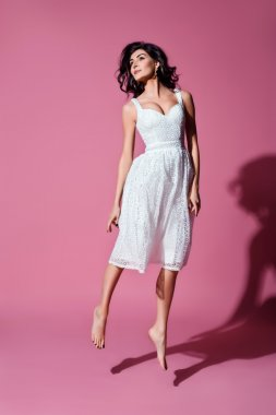 young beautiful brunette woman in a white white dress in the studio on a pink background