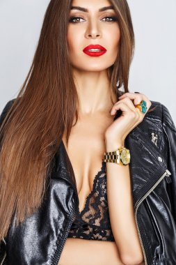 beautiful young brunette woman with red lips in a black leather jacket in the studio on a white background