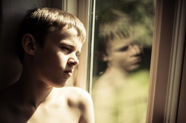 Sad shirtless child reflected in window