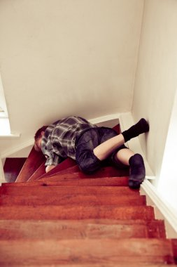 Young boy lying sprawled on a staircase