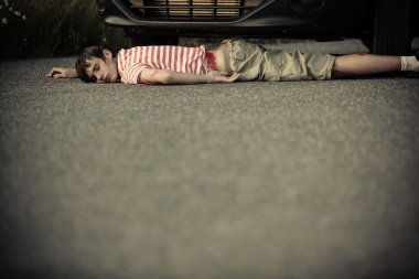 Child with bloodied hip near front of car