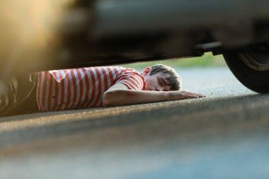 Hurt and unconscious child on asphalt