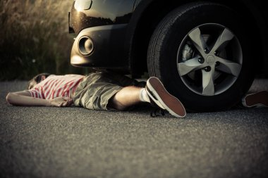 Dead child laying on street in front of car