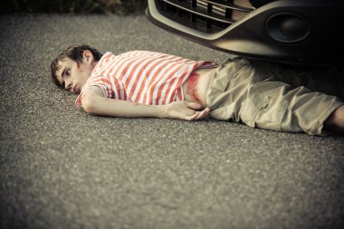 Boy with cut hip laying down in front of car