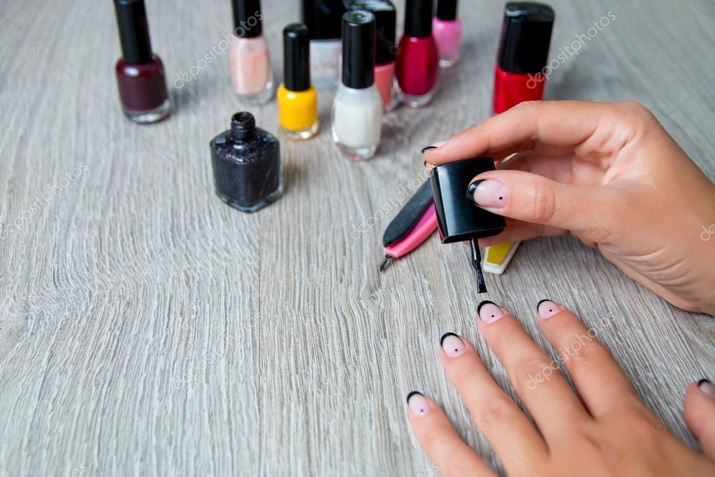 Esmalte de uñas negro se aplica a mano con herramientas para ...