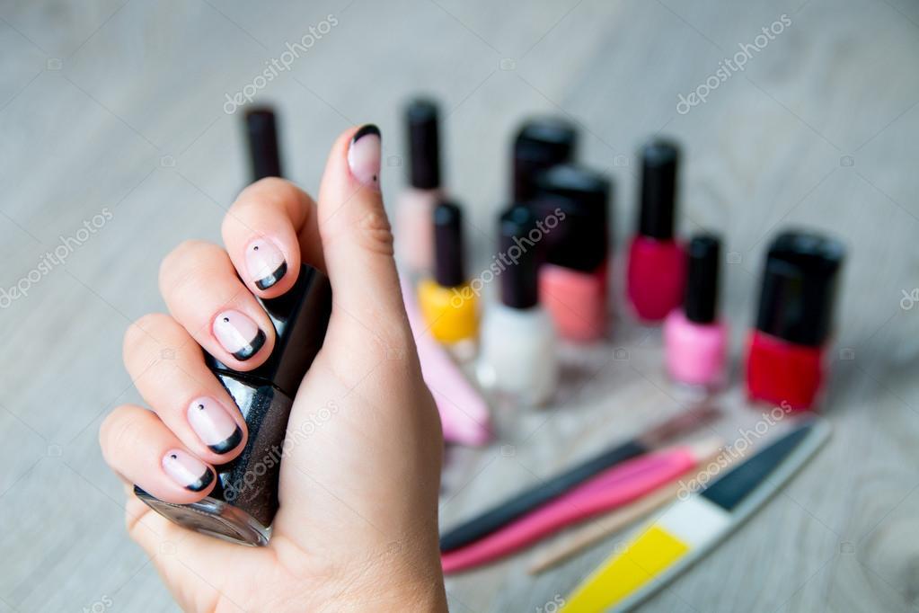 Esmalte de uñas negro en mano femenina con herramientas para ...