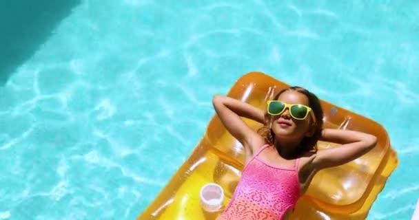 A kislány napszemüvegben lazít a medencében, élvezi a napbarnítást, felfújható sárga matracon úszik.