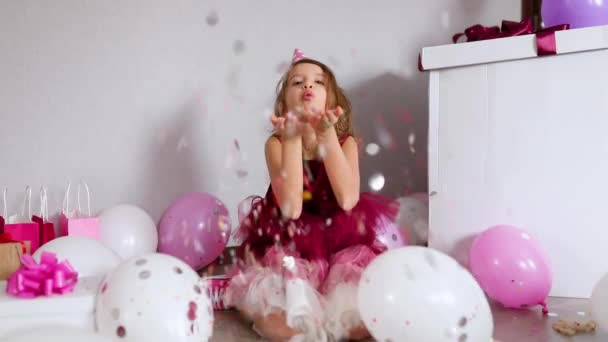 Slow motion beautiful little girl blows up multicolored confetti, having fun at home birthday party. Happy birthday child.