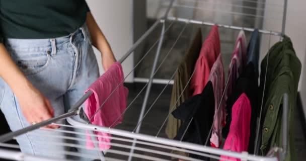Hausfrau faltet Kleidung nach dem Waschen zu Hause vom Wäscheständer, drinnen, Frauenhände, tägliche Hausreinigung