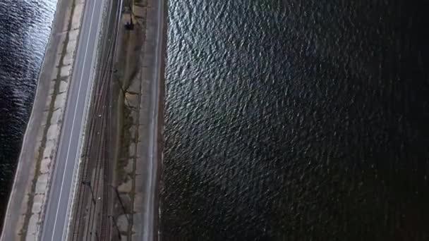 Pohled na krajinu asfaltové silnice s auty jedoucími podél modré řeky. Pohled shora, Letecký pohled na venkovskou silnici.