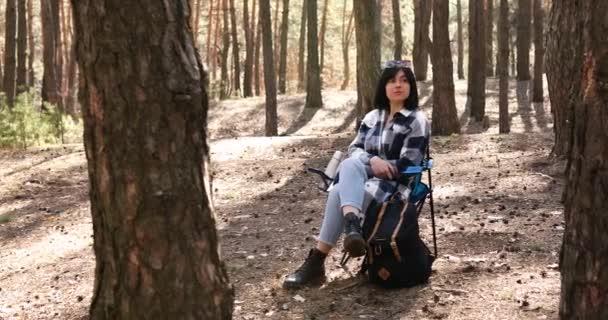 Relax, klidná žena hluboké dýchání odpočinku, posezení v křesle s turistickým batohem v borovém lese v slunečním svitu jarní den, relaxace a zdravý životní styl koncept, dostat ven.