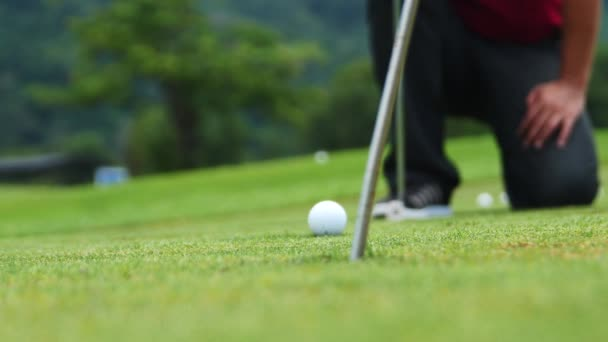 Golf player strikes ball on golf course