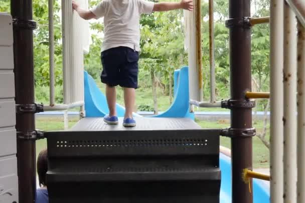 Malý chlapec rád hraje v dětské hřiště