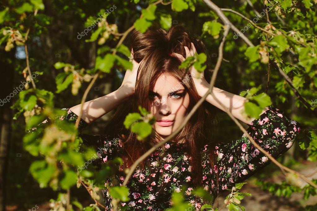 Young brunette woman posing near green tree in sunlight