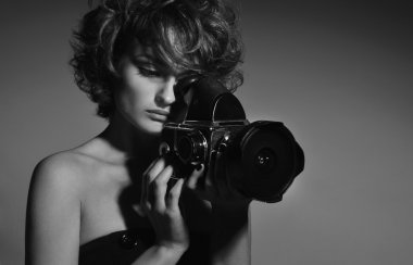 Black and white photo of beautiful woman with photo camera