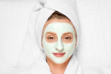 Beauty Treatments. Woman applying facial mask at spa