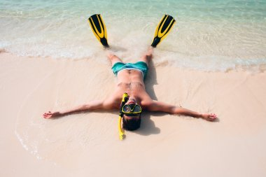 Man, relaxing in yellow black flippers fins and mask.