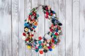 Ručně vyráběné světlé barevné šperky vyrobené z plastových tlačítek na bílém pozadí dřevěná