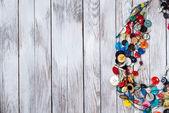 Ručně vyráběné světlé barevné šperky vyrobené z plastových tlačítek na bílém pozadí dřevěná. Místo pro text