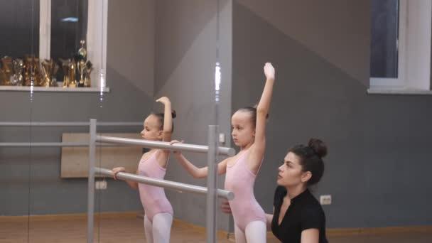 Fiatal tanár kis balerinákat tanít egy táncórán a stúdióban.