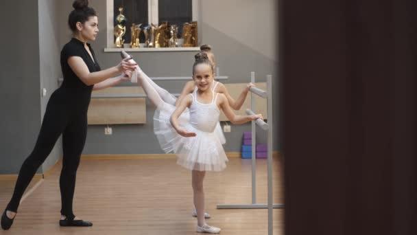 Junge Lehrerin unterrichtet kleine Ballerinen bei einem Tanzkurs im Studio