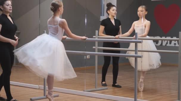 Balet učitel profesionální balerína pomáhá dívka vlak v blízkosti barre