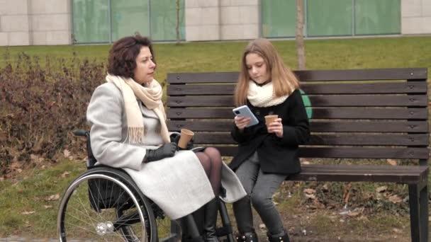 Schulmädchen mit ihrer behinderten Mutter beim Teetrinken draußen