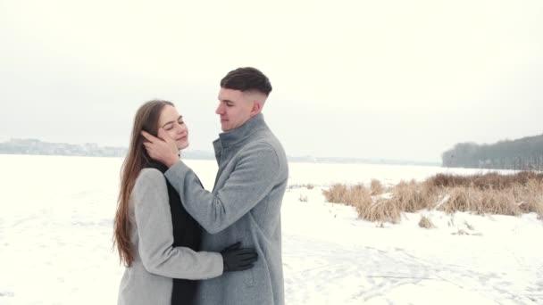 Liebespaar in Plaid gehüllt sitzt im Winter draußen