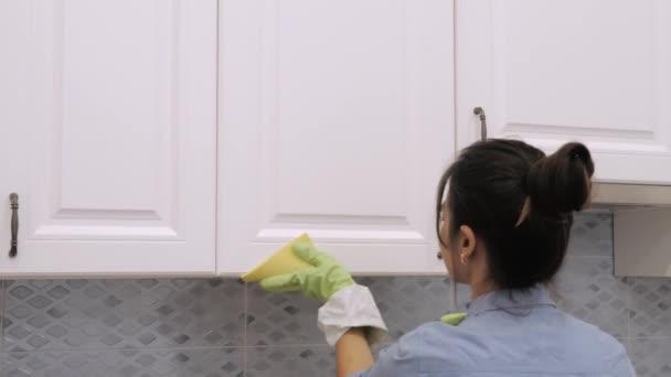 Čistič nebo hospodyně mytí kuchyňského nábytku s hadrem