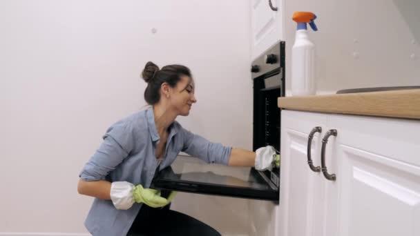 Junge Frau putzt Backofen in der Küche