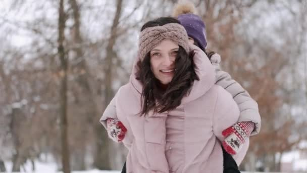 Happy European mother and her little daughter having fun in winter forest
