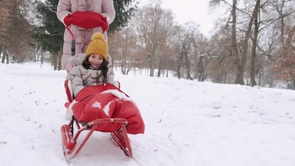 Mutter und Tochter im Winter beim Schlittenfahren im Park