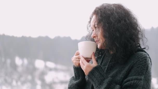 Středního věku žena s kudrnaté vlasy pít kávu na balkóně horského hotelu
