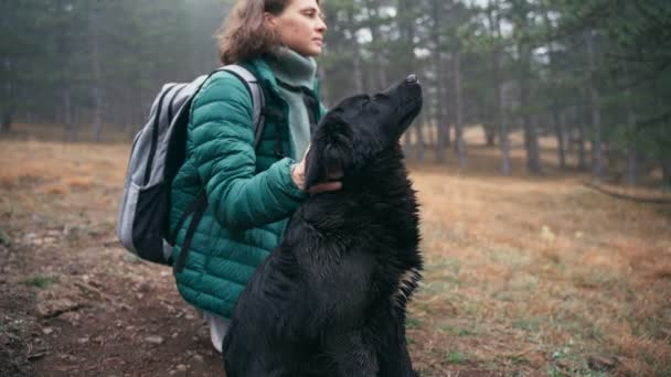 Young woman stroking her cute black dog while walking her in the autumn forest