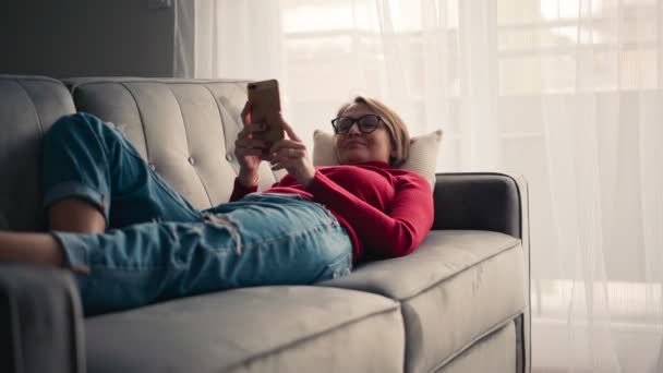 A young woman in glasses lying on the couch with a smartphone in hands