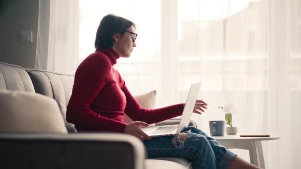 Mladá žena pracuje na svém notebooku a pije kávu, zatímco sedí na gauči