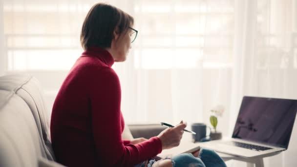 Žena středního věku v brýlích si dělá poznámky do sešitu.