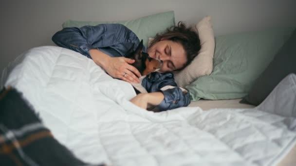 Mladá žena se probudí a leží v posteli se psem pod peřinou.