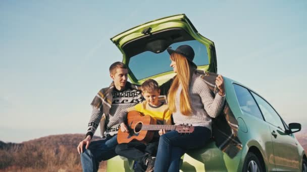 Family plays guitar and sings songs while sitting on the hatchback of the car