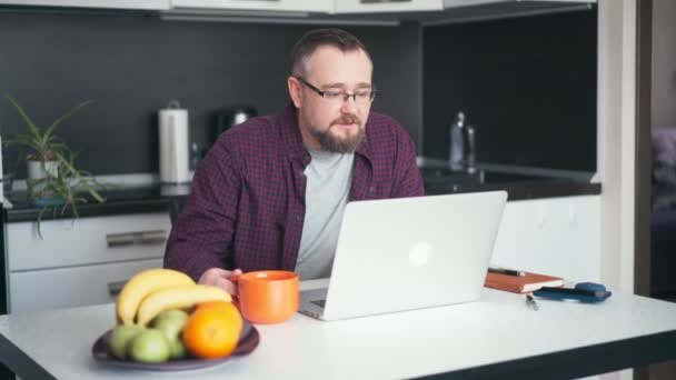 An adult handsome bearded man freelancer working from home.