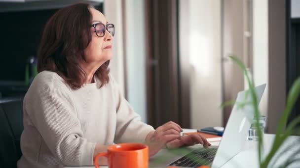 A senior woman in glasses working at home with a laptop and drinking coffee